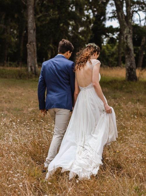 Photograph of a young man and woman walking through a field for an elopement wedding shoot
