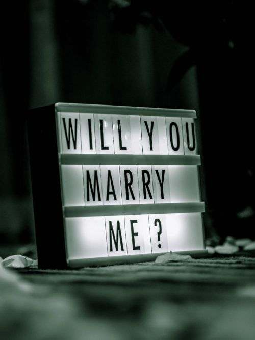 An illuminated sign saying 'Will You Marry Me' used for filming a marriage proposal