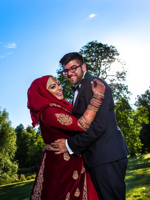 A Muslim groom and his bride wearing a hijab having a picture taken on their wedding day