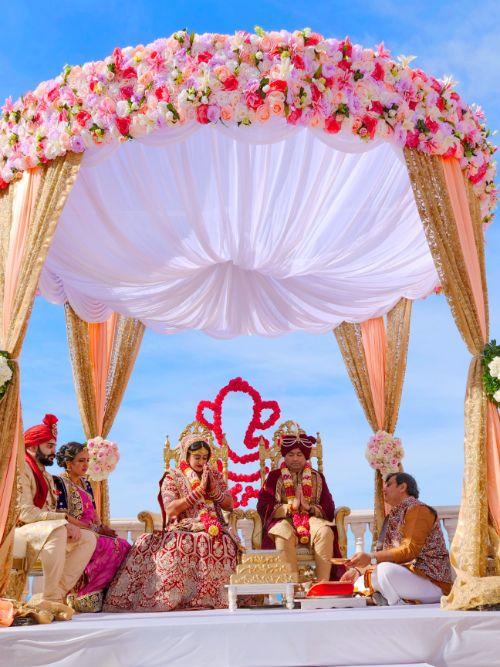 In Indian bride and groom sitting under a mandap whilst their Hindu wedding ceremony is filmed