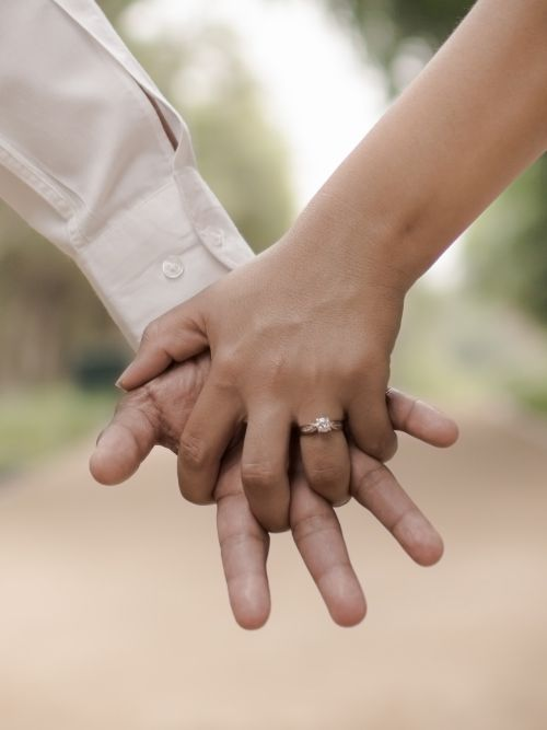 A couple holding hands and showing their engagement ring during filming of their pre-wedding video