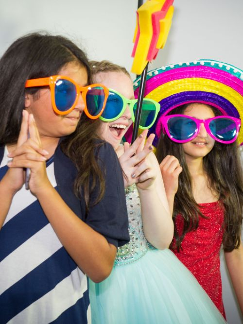 Three children wearing funny glasses and hats being filmed at a kid's party