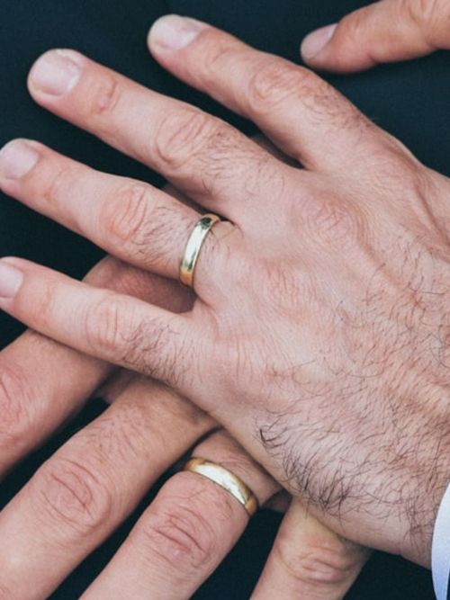Same sex couple placing hands on top of one another to show their wedding rings