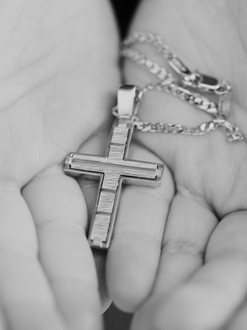 Christening gift of a Christian cross necklace in the palm of a priest's hand