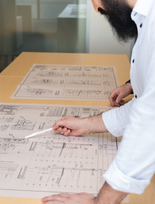 A man reviewing plans on a table