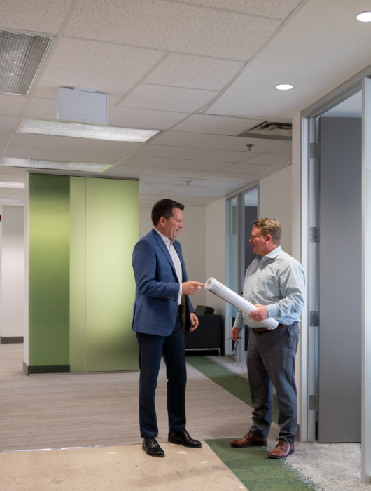 David Leighton and Dave Walker conversing in a hallway