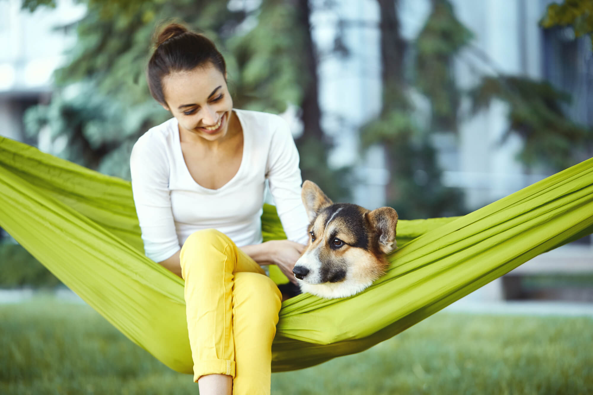 woman smiling in hammock with dog