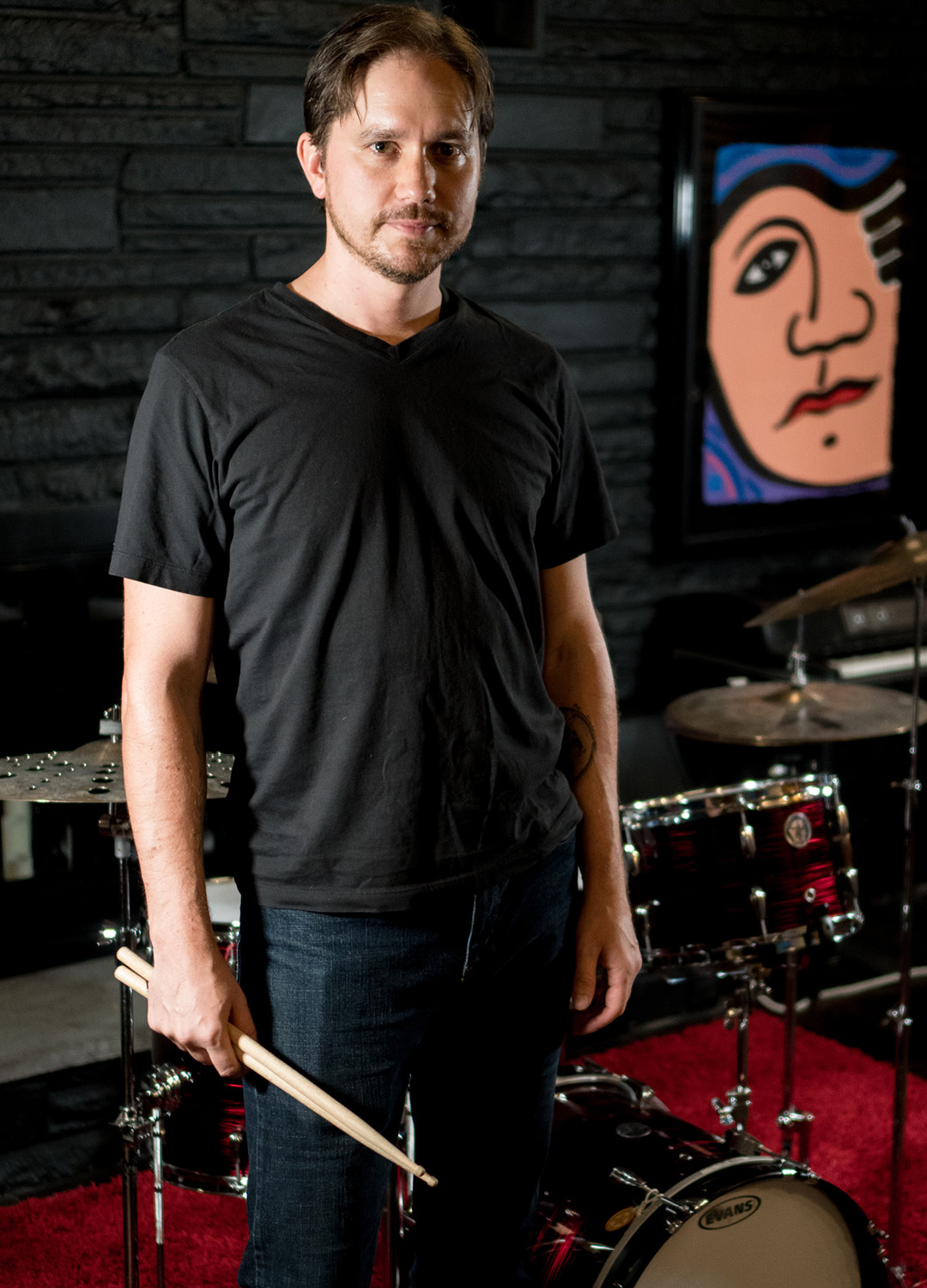 man standing holding drumsticks in front of drum kit