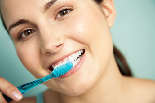 Woman brushing teeth as preventive action after advice from Shenandoah Family Dentistry