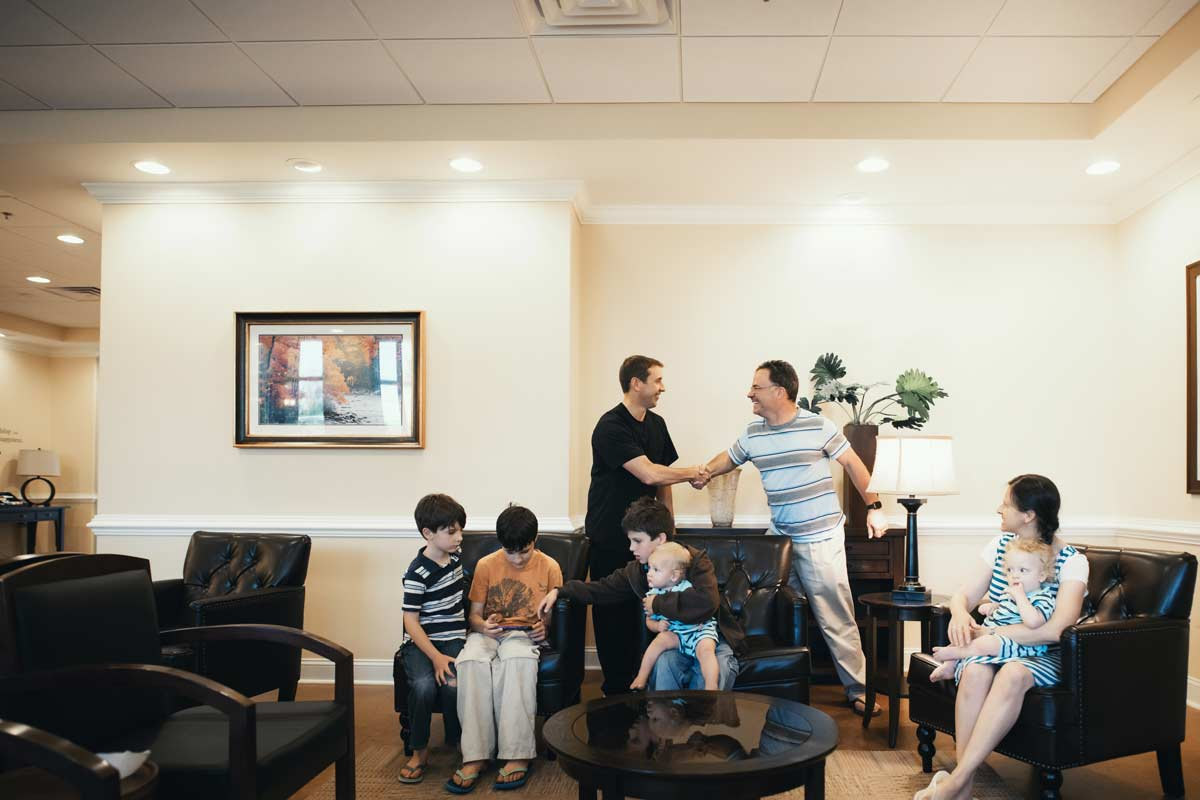 Photo of Dr. Pell shaking a patient's hand, with kids in the lobby