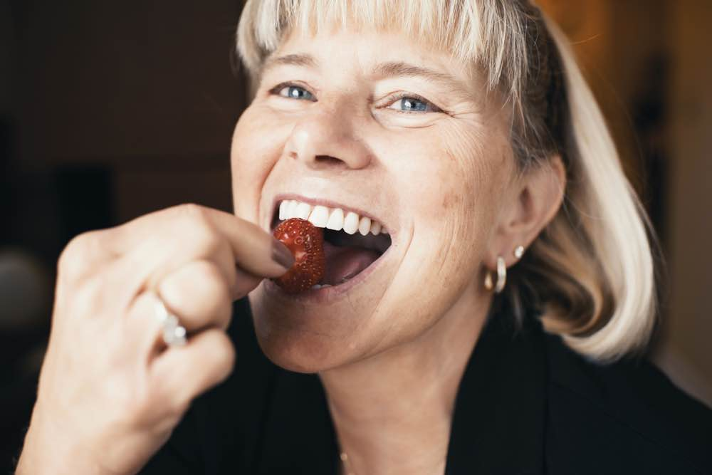 Photo of a woman eating a strawberry
