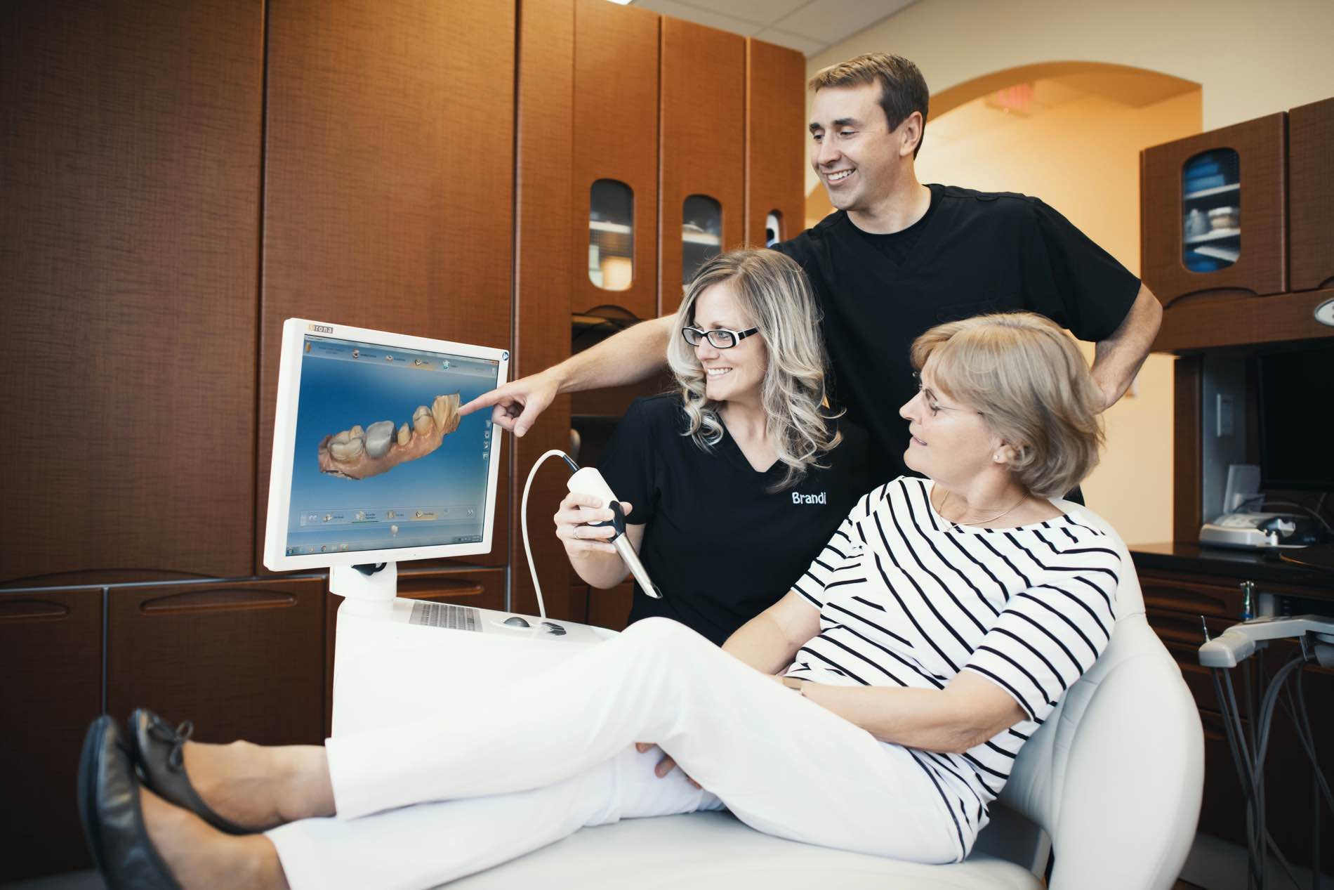 Photo of Dr. Pell pointing at a dental scan on a monitor while a patient and team member observe