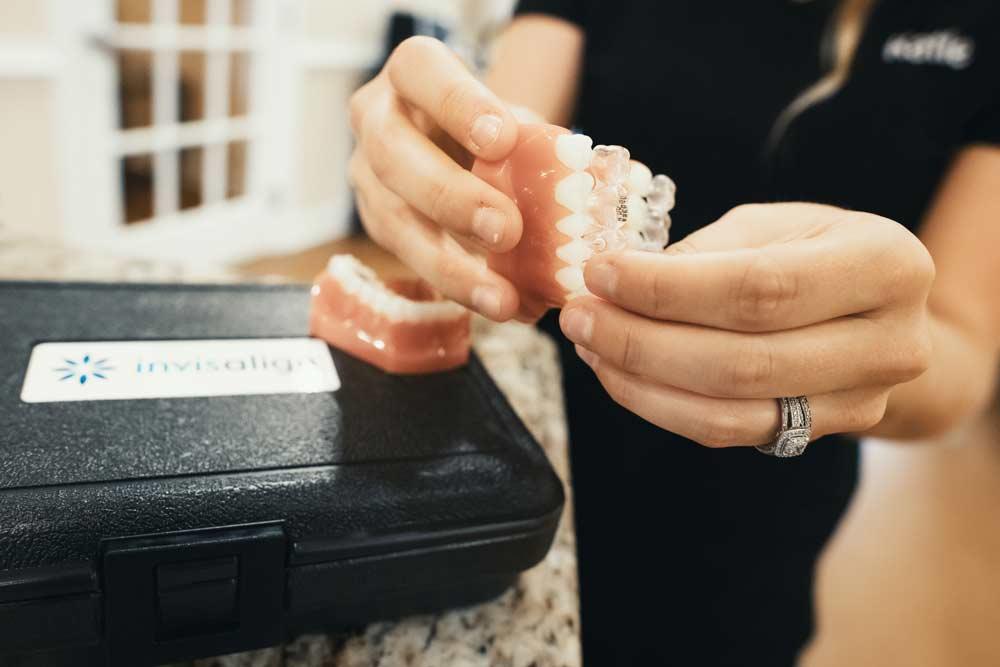 Photo of hands holding an Invisalign aligner on a dental model