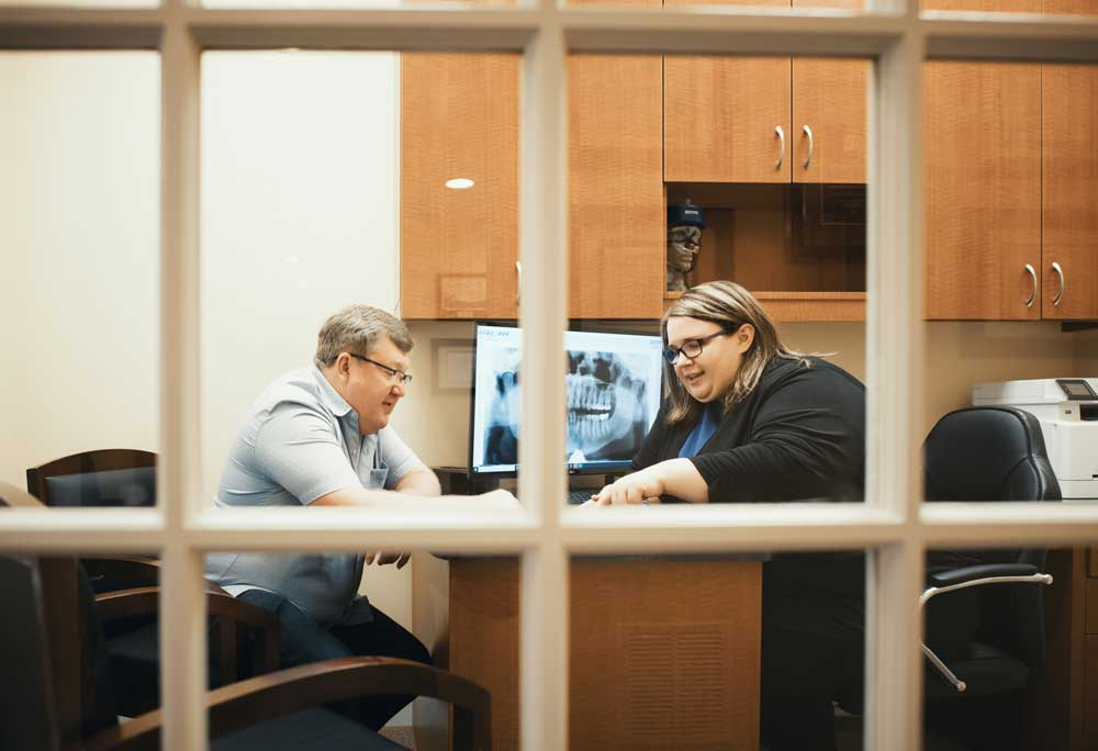 Photo of a team member and a patient sitting at a desk