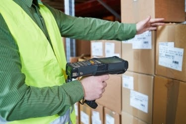 Man using a Warehouse Management System device to scan a box