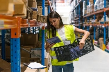 Woman picking an item in a warehouse