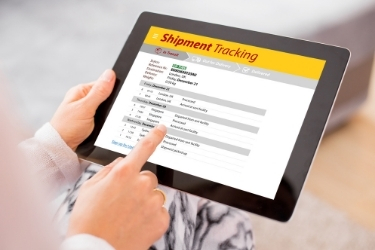 """Woman holding a tablet with a """"Shipment Tracking"""" software"""