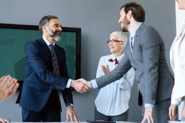 Businessmen handshaking and people applauding