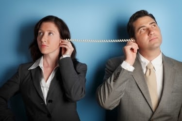 Woman and Man looking at opposite sides both holding a side of a telephone chord.