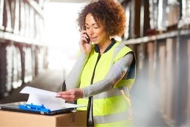 Woman inside a warehouse making phone calls