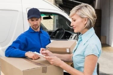 Woman receiving delivery and signing papers