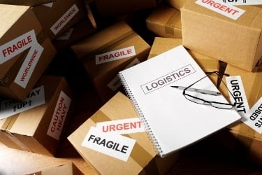 """Pile of boxes and a notebook that says """"Logistics"""""""