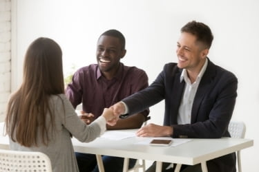 Two men interviewing a woman for hiring