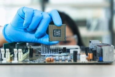 Woman holding a chip and a mother board