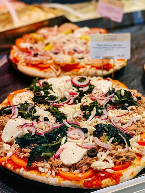 verschiedene Pizzen in der Theke zur Auswahl