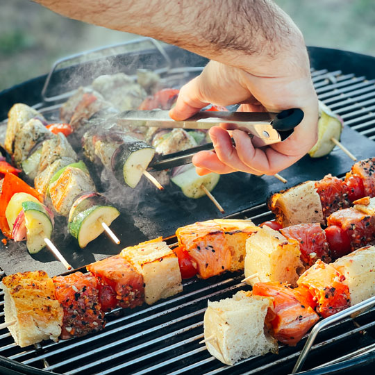 Ein Mann grillt und wendet die Portola Grillspieße auf dem Grillrost