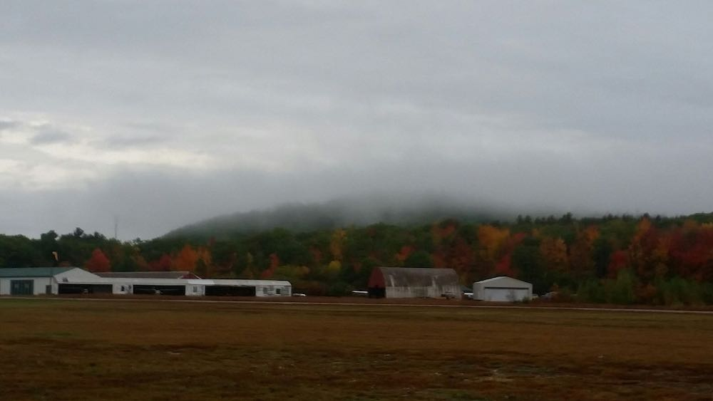 View of hangars, fog and fall colors at Twitchell's.