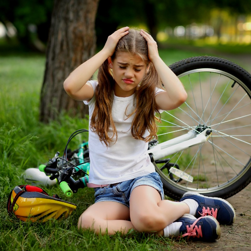 a girl holding her head after falling off bike