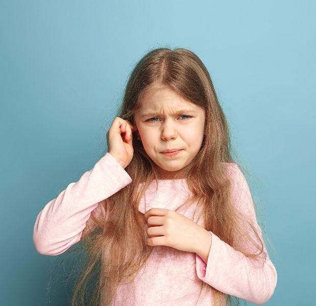 little girl holding her ear