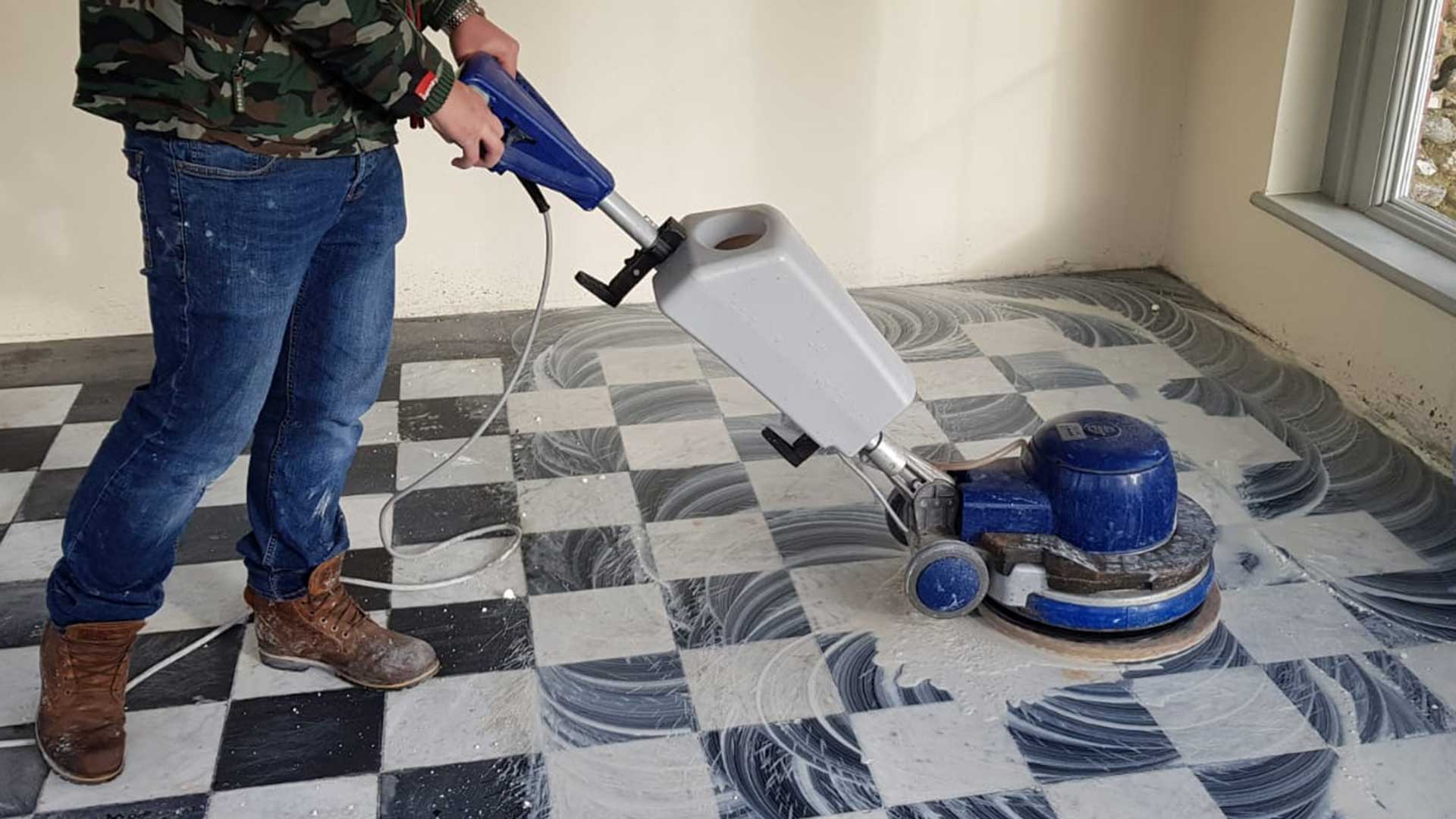 Operative using a floor cleaner on tiled floor