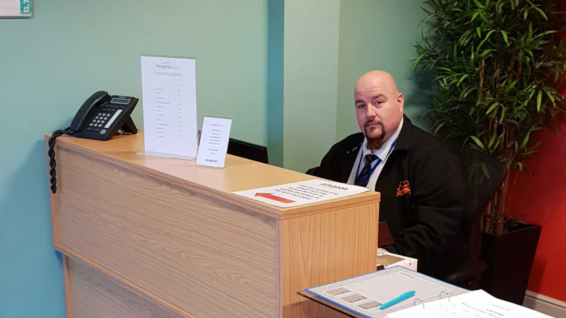 AP security guard manninng reception desk