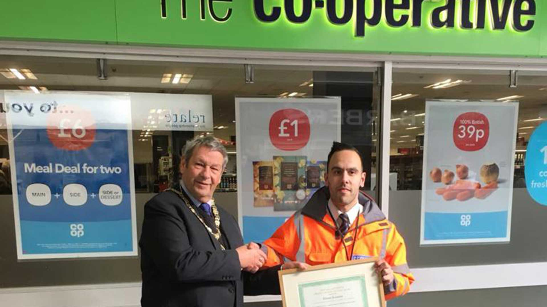 Security guard picking up award at Co-Op
