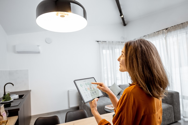 woman using a tablet to set smart lighting mood makers at home