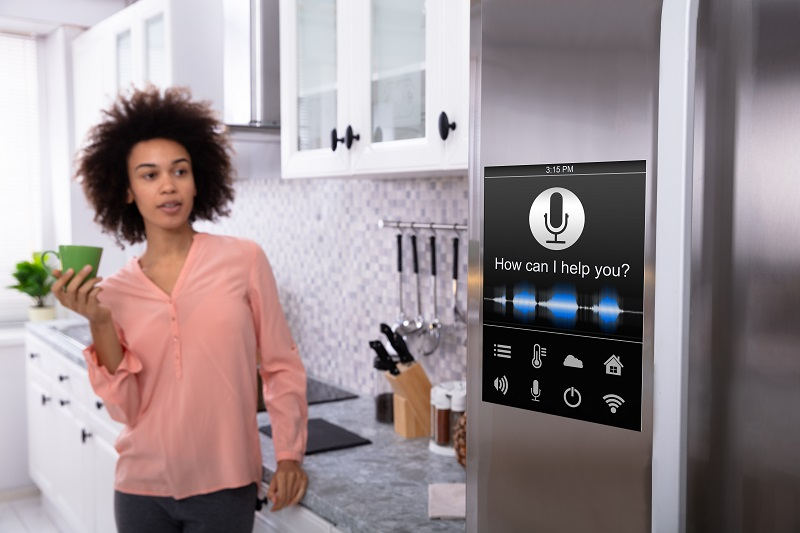 woman speaking to an virtual assistant which is integrated in the kitchen fridge