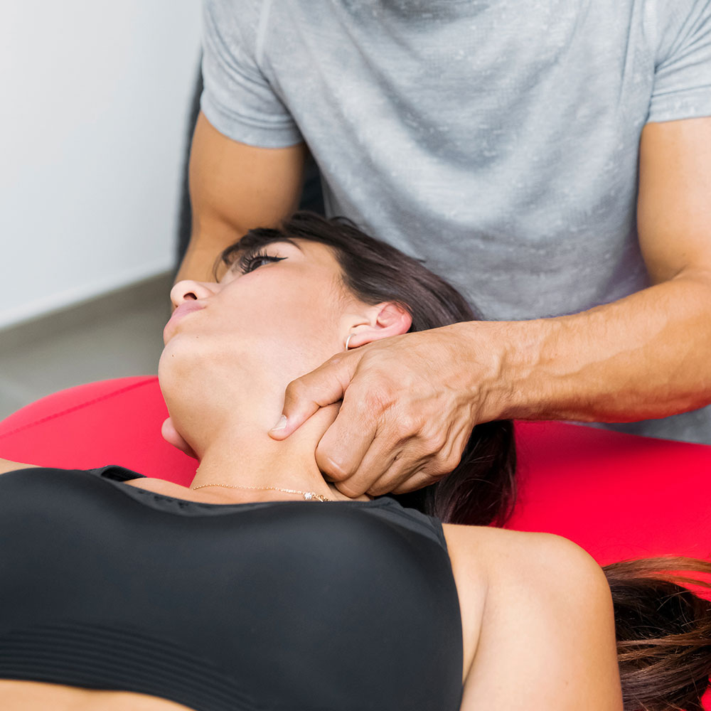 Chiropractor performing an alignment on a young woman for headache and migraine relief.