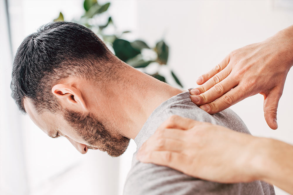 Chiropractor adjusting male patient neck