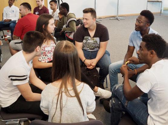 Foto von Jugendlichen, die in der Gruppe diskutieren