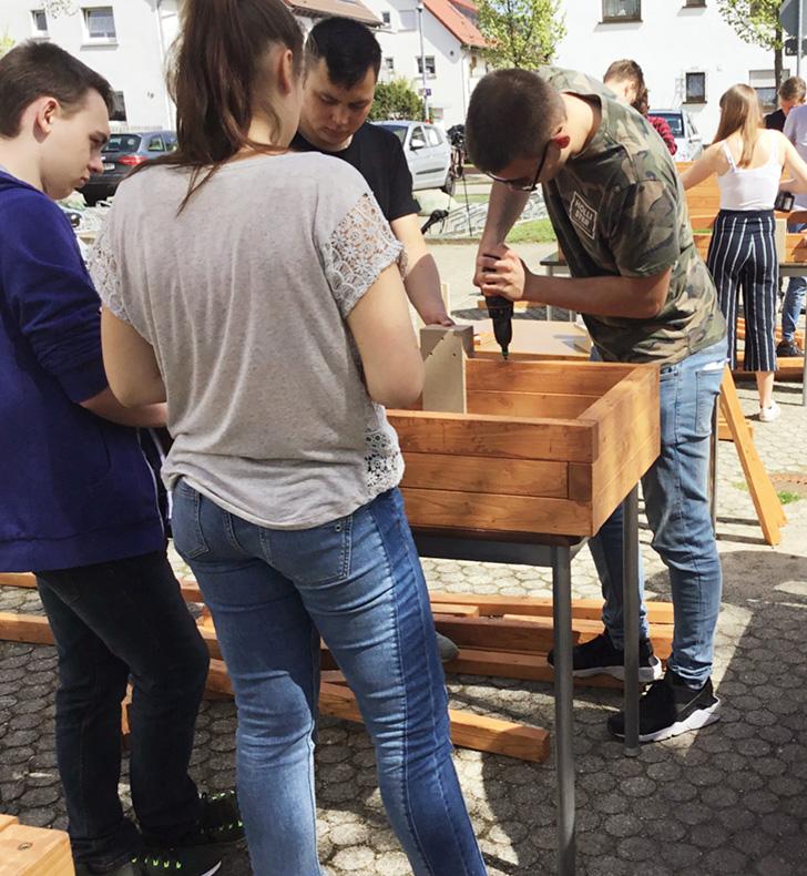 Foto von Jugendlichen, die eine Holzkiste bauen
