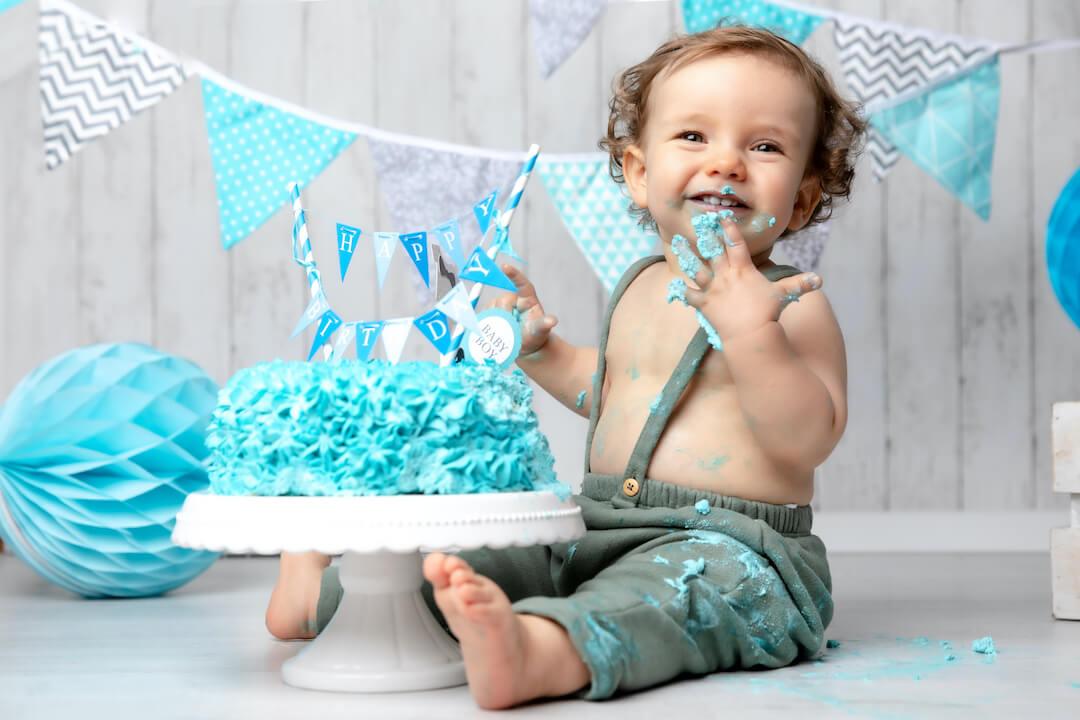 Kleiner Junge isst eine Torte auf einem Willkommensfest.