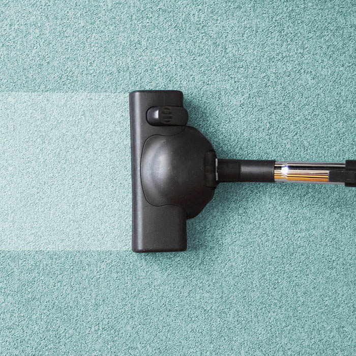 vacuum going across carpet with clean strick