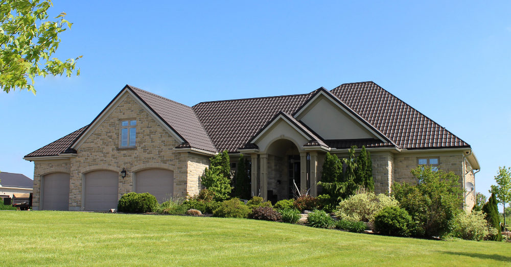 A brown brick home with a brown metal roof.