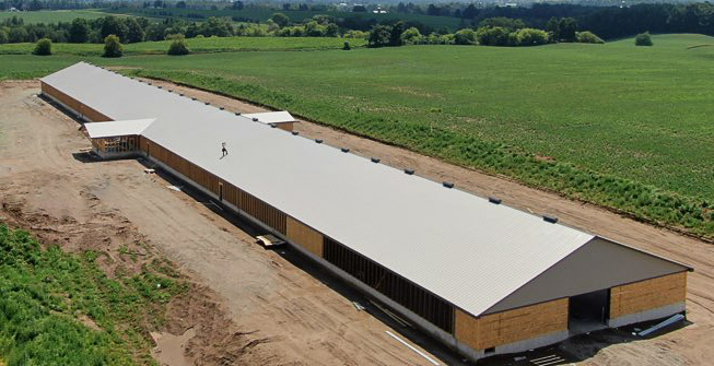A long barn under construction with a light metal roof.