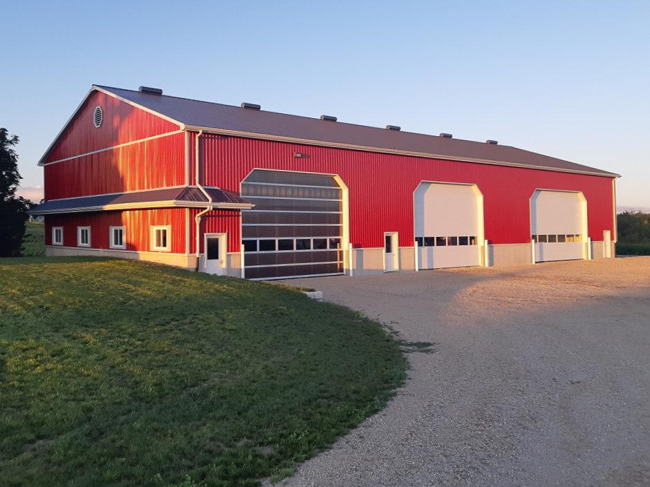 Red three-garage barn with dark metal roof.