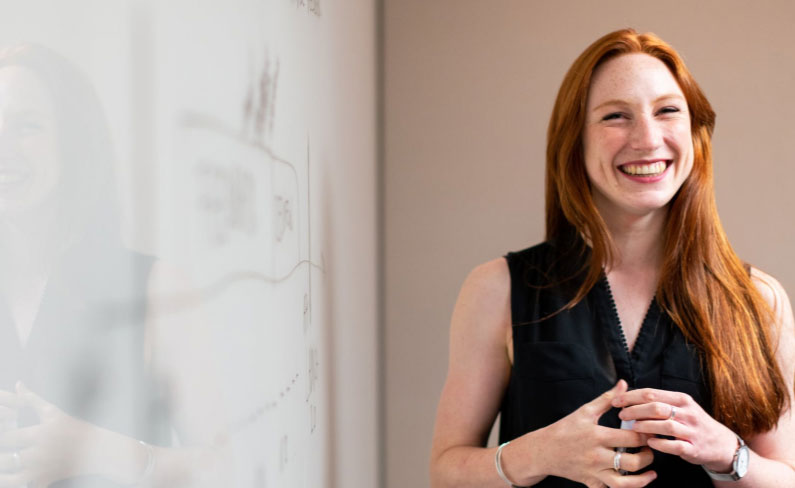 Image of a woman similing with a whiteboard in the background showing some design and content ideas