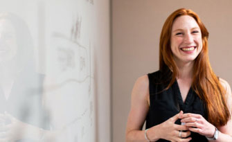 Image of a woman smiling with a whiteboard in the background showing some design and content ideas