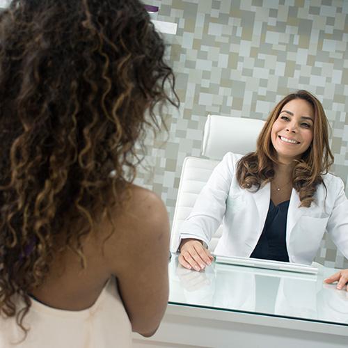 Dermatóloga sonriente atendiendo a una paciente mujer en su consultorio